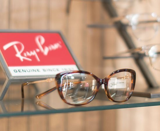 ray ban glasses in front of branded sign
